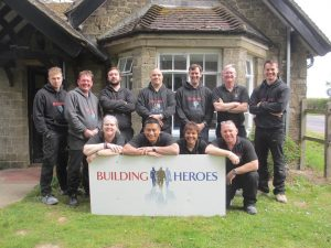 An image of our graduate tradespeople next to a large Building Heroes sign