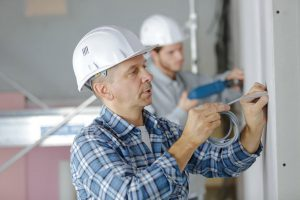 An image of two electricians drilling holes