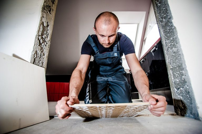 An image of a tradesperson laying floor tiles