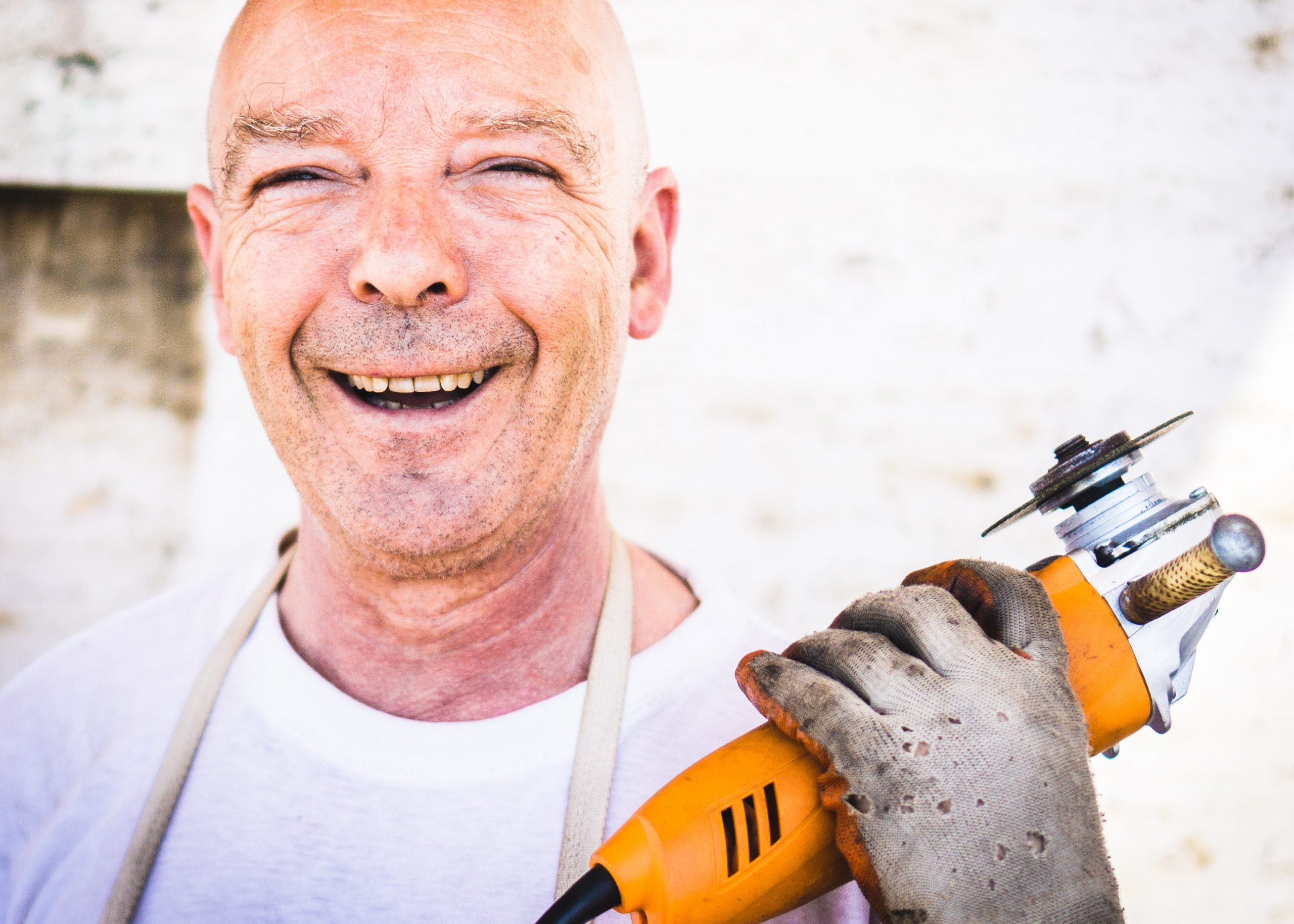 An image of a happy tradesperson holding a drill