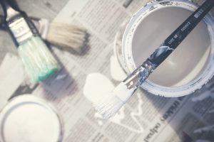 An image of a paint tin and brush used for decorating